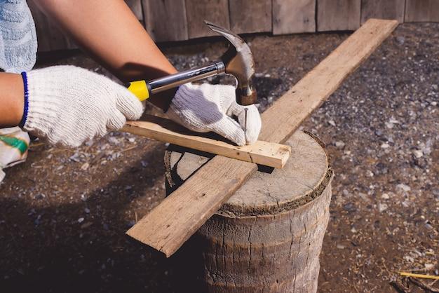 Bauarbeiter im blauen hemd mit schutzhandschuhen, die mit hammer arbeiten