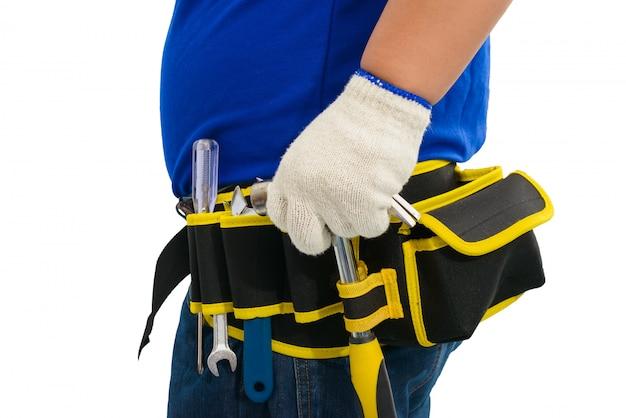 Bauarbeiter im blauen hemd mit schutzhandschuhen, helm mit werkzeuggürtelhand, der hammer lokalisiert auf weiß hält