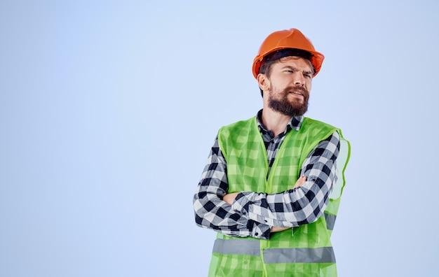 Bauarbeiter im orangefarbenen schutzhelm auf blauem hintergrund und reflektierende weste des karierten hemdes. hochwertiges foto