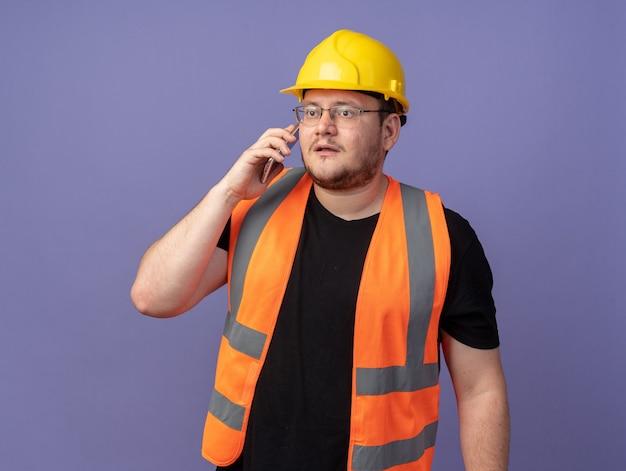 Bauarbeiter in bauweste und schutzhelm, der auf dem handy spricht und mit ernstem gesicht beiseite schaut