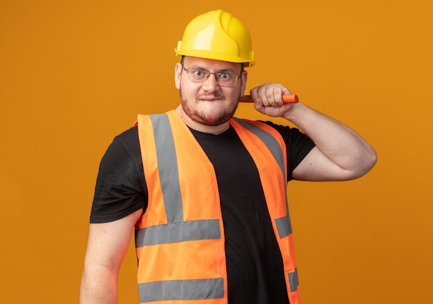 Bauarbeiter in bauweste und schutzhelm, der hammer mit wütendem gesicht in die kamera schaut