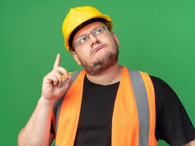 Bauarbeiter in bauweste und schutzhelm, der verwirrt nach oben zeigt und mit dem zeigefinger über grün steht