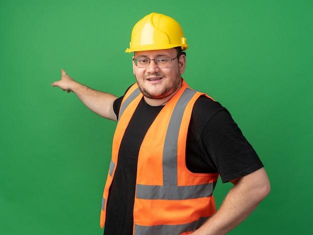 Bauarbeiter in bauweste und schutzhelm mit blick auf die kamera lächelt zuversichtlich und zeigt mit dem zeigefinger zurück, der über grünem hintergrund steht