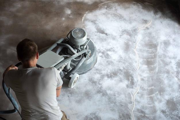 Bauarbeiter in einem familienheimwohnzimmer, das die betonoberfläche reibt, bevor epoxidbodenbelag angewendet wird polyurethan und epoxidbodenbelag konkretes schleifen.