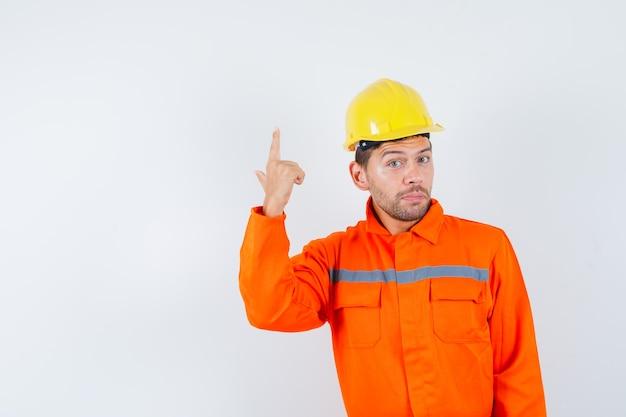 Bauarbeiter in uniform, helm zeigt nach oben und sieht selbstbewusst aus, vorderansicht.