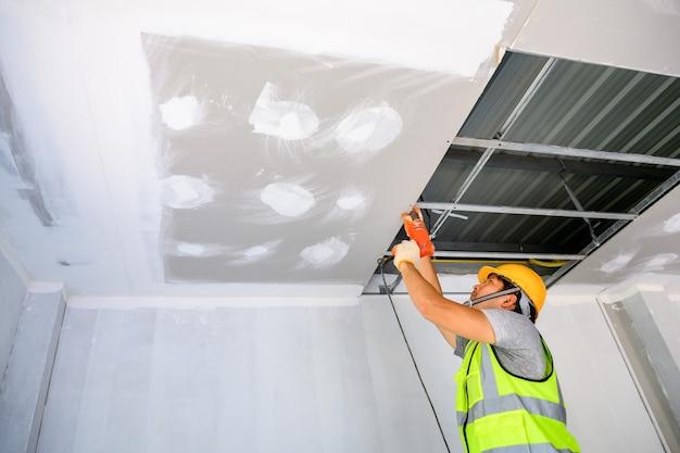 Bauarbeiter in uniform installieren sie eine gipsdecke im inneren des hauses und des gebäudes. verwenden sie einen elektrischen schraubendreher, um die decke zu installieren.