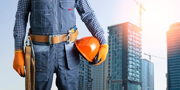 Bauarbeiter in uniform mit sicherheitsgurt und helm auf der baustelle.