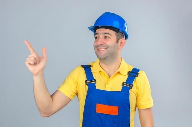 Bauarbeiter in uniform und blauem schutzhelm mit glücklichem gesicht, das oben mit finger lokalisiert auf weiß zeigt