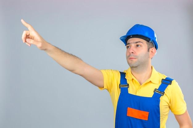 Bauarbeiter in uniform und blauem schutzhelm zeigt mit dem zeigefinger seitlich auf isoliertes weiß