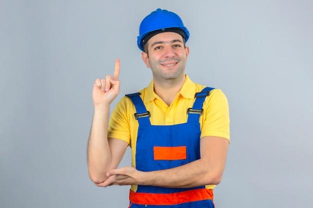 Bauarbeiter in uniform und blauem sicherheitshelm, der mit positivem lächeln des fingers oben lokalisiert auf weiß zeigt
