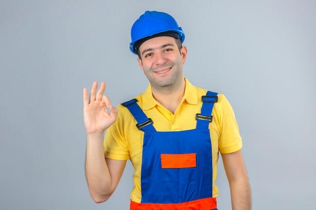 Bauarbeiter in uniform und blauem sicherheitshelm lächelnd positiv, das ok zeichen lokalisiert auf weiß