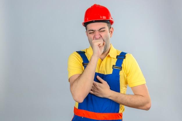 Bauarbeiter in uniform und rotem schutzhelm gelangweilt, gähnender müder kegelmund mit hand lokalisiert auf weiß