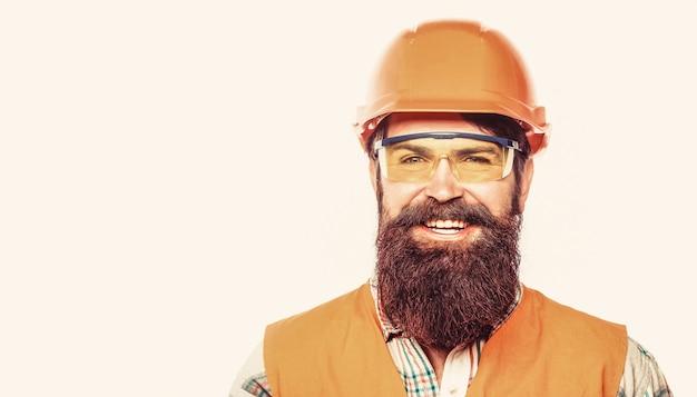 Bauarbeiter, industrie. baumeister im schutzhelm, vorarbeiter oder mechaniker im helm. bärtiger arbeiter mit bart beim bau von helm oder schutzhelm. porträt eines erbauerlächelns.