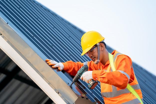 Bauarbeiter installieren neues dach, dachdecker arbeitet an der dachkonstruktion des gebäudes auf der baustelle.