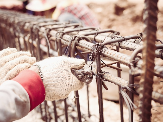 Bauarbeiter installieren stahlstangen in stahlbetonträger