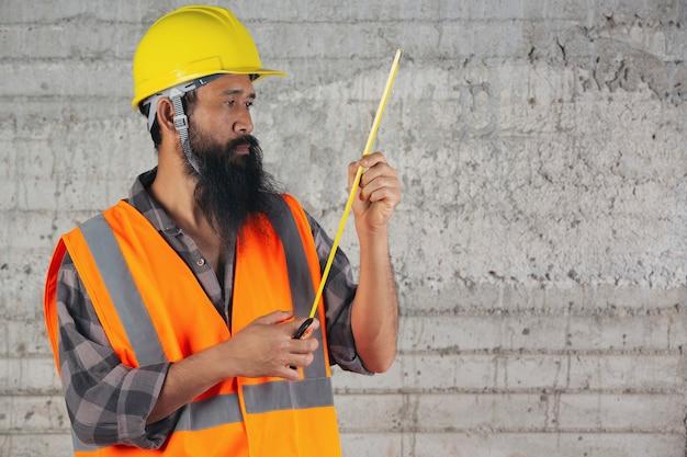 Bauarbeiter ist maßband und denkt über plan auf der baustelle nach.