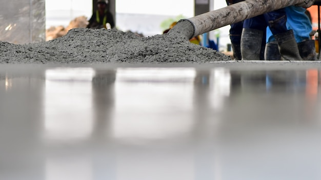 Bauarbeiter konkretes gießen während der handelsbetonierungsböden