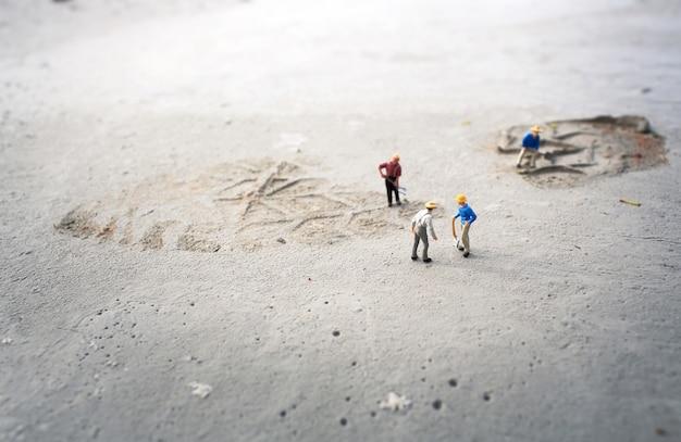 Bauarbeiter (miniatur) auf betonboden. flache schärfentiefe und vintage-farbe.
