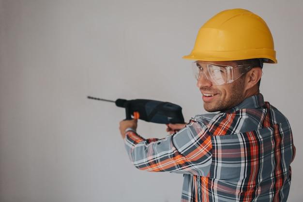 Bauarbeiter mit ausrüstung, die loch in wand auf der baustelle macht