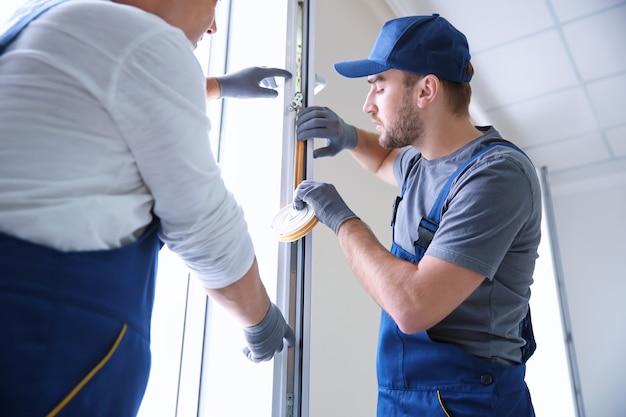Bauarbeiter mit auszubildender, der fenster im haus einbaut