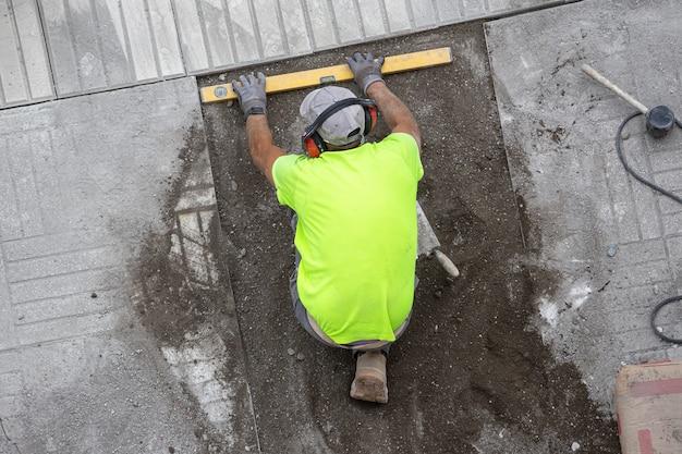 Bauarbeiter mit bauebene, die auf einem bürgersteig arbeitet. wartungskonzept