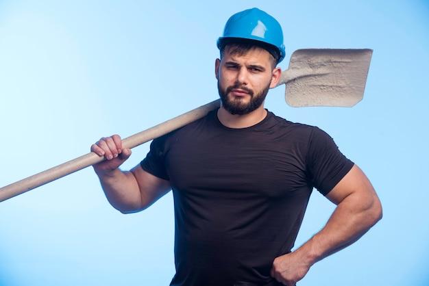 Bauarbeiter mit blauem helm, der die ausrüstung hält