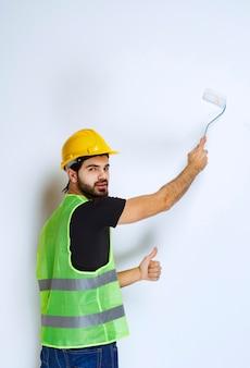 Bauarbeiter mit gelbem helm, der die weiße wand mit einer trimmwalze malt.