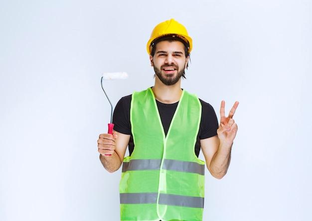 Bauarbeiter mit gelbem helm, der eine weiße zierrolle hält.