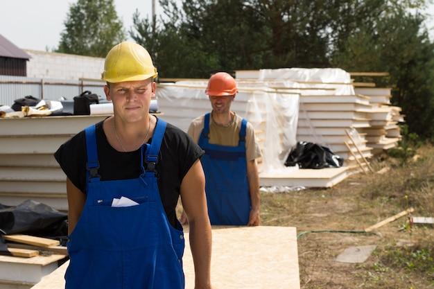 Bauarbeiter mit isolierten holzwandpaneelen auf einer baustelle, die sich der kamera nähert