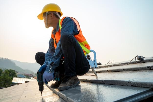 Bauarbeiter mit nagelpistole, der neues dach im im bau befindlichen gebäude installiert.