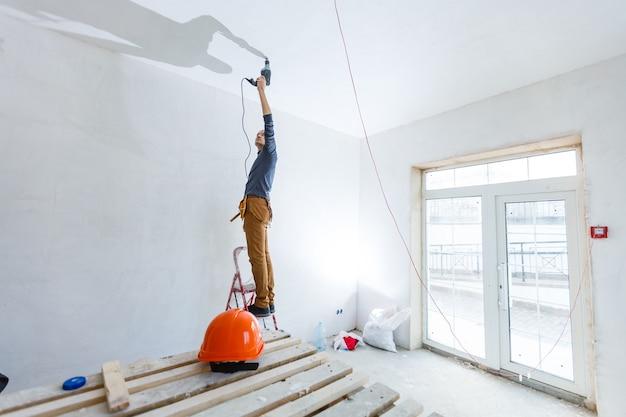 Bauarbeiter mit pneumatischer hammerbohrer-perforatorausrüstung, die auf der baustelle ein loch in der wand macht