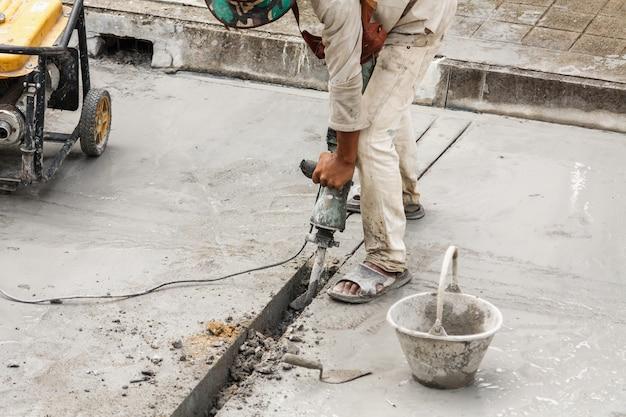 Bauarbeiter mit presslufthammer, der betonoberfläche bohrt