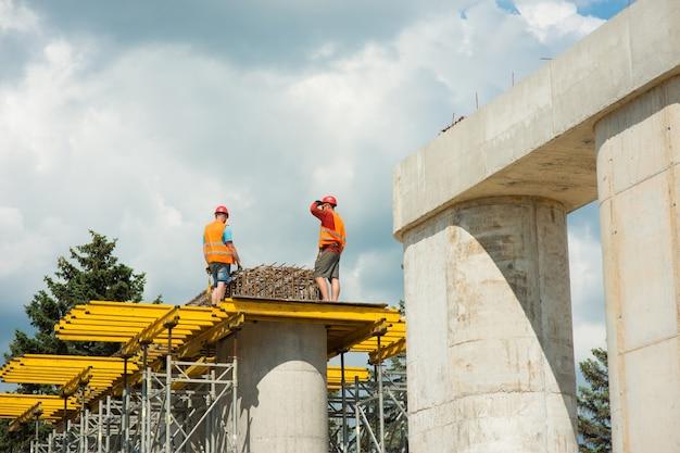 Bauarbeiter mit schutzhelmen montieren beim bau einer straßenbrücke verstärkte rahmen auf betonsäulen.