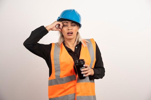 Bauarbeiter mit tasse tee, der schläfrig fühlt. hochwertiges foto