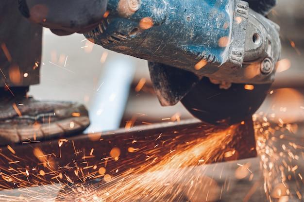 Bauarbeiter mit winkelschleifer beim schneiden von metall auf der baustelle.