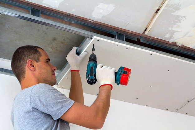 Bauarbeiter montieren eine abgehängte decke mit trockenbauwand und befestigen die trockenbauwand mit einem schraubendreher am metallrahmen der decke.