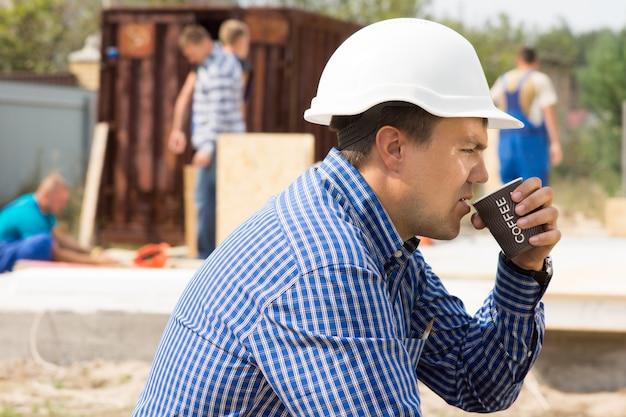 Bauarbeiter oder bauarbeiter sitzend bei einer tasse kaffee vor ort mit seinen kollegen, die im hintergrund arbeiten, seitenansicht side