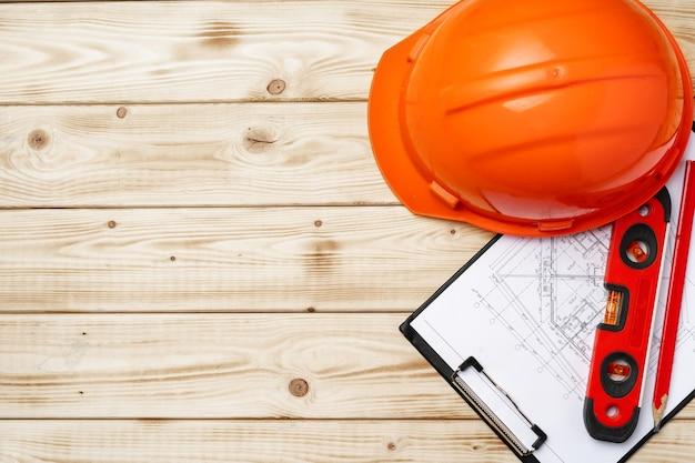Bauarbeiter-schutzhelm, blaupausen und konstruktionsniveau, draufsicht auf hölzernem hintergrund