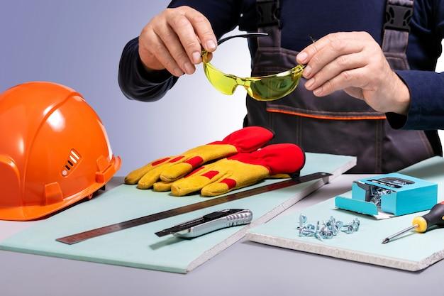 Bauarbeiter setzt schutzbrille auf. konzept sicherheitsausrüstung.