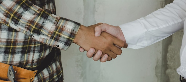 Bauarbeiter-team-auftragnehmer-händedruck mit ingenieur, nachdem geschäftstreffen beendet worden ist, um projektvertrag im baustellegebäude zu beginnen