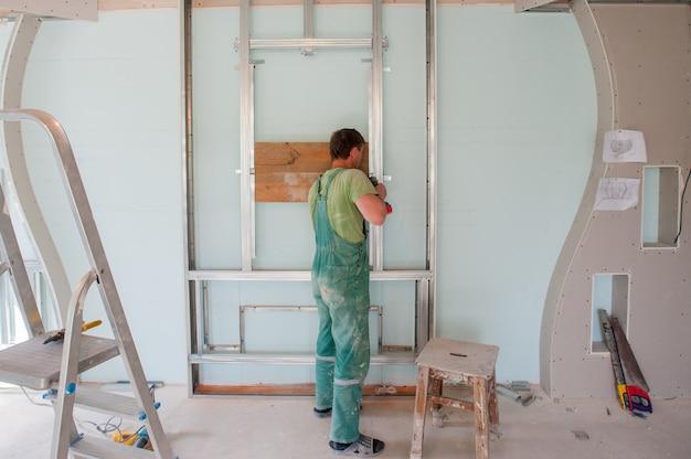 Bauarbeiter tragen einheitliche installationsdeckenarbeit der sicherheit