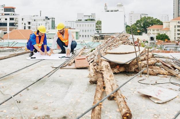 Bauarbeiter überprüfen blaupause