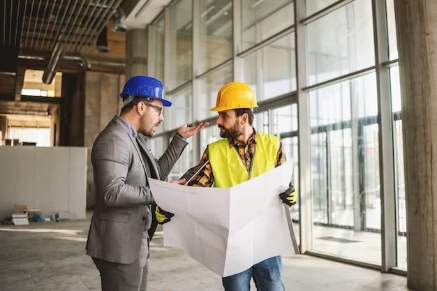 Bauarbeiter und architekt streiten über arbeiten. architekt schreit arbeiter an. innenraum der baustelle.