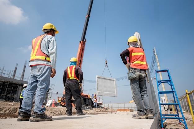 Bauarbeiter und ingenieur, die mobilen kran schauen, herauf fertigbetonmauer