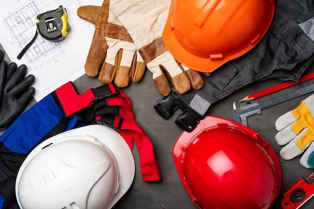 Bauarbeiter unifrom, helm und blaupausen auf hölzernem hintergrund, draufsicht