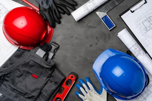 Bauarbeiter unifrom, helm und blaupausen auf hölzernem hintergrund