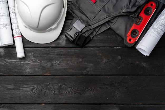 Bauarbeiter unifrom, helm und blaupausen auf holz, draufsicht