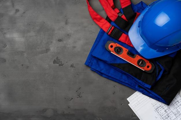 Bauarbeiter unifrom, helm und blaupausen auf holz