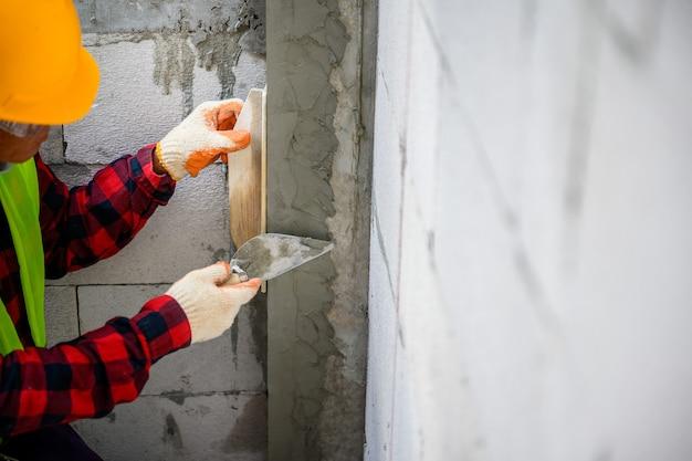 Bauarbeiter verputzen von leichtbetonwänden verputzen im bau hausputztechniken basic auf der baustelle.