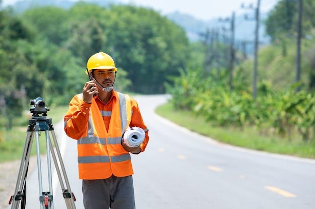 Bauarbeiter verwenden theodolit-zeichen auf der straße, bauingenieure verwenden einen höhenmesser auf der baustelle.